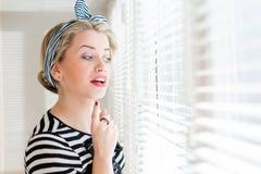 Schöne blonde Pinupfrau, die durchdacht durch Jalousiefenster schaut Stockbild