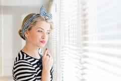 Schöne blonde Pinupfrau, die durchdacht durch Jalousiefenster schaut Lizenzfreies Stockfoto