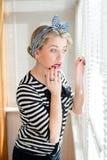 Schöne blonde Pinupfrau, die durchdacht durch Jalousiefenster schaut Lizenzfreies Stockbild