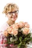 Schöne, blonde reife Frau mit Rosen Stockbilder