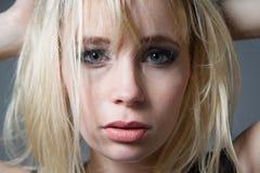 Schöne blonde schauende Kamera der blauen Augen Stockfotos