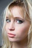 Schöne blonde schauende Kamera der blauen Augen, zuhause Stockbild