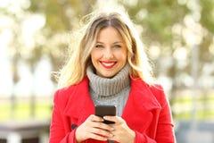Schöne blonde schauende Kamera, die ein intelligentes Telefon hält Stockfotos