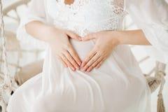 Schöne blonde schwangere Frau, die am Schwingen mit Blumen sitzt Stockfotos