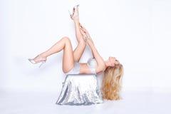Schöne blonde sexy Frau im verlockenden sinnlichen glänzenden silbernen Kleid liegt auf einem Würfel mit Kristallen mit den lange Lizenzfreies Stockbild