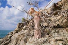 Schöne blonde sexy Frau mit den langen Beinen im fantastischen Kristallkleid, das auf den Felsen übersehen das blaue Meer steht Stockfoto