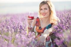 Schöne blonde sexy Frau trinkt roten trockenen Wein auf dem Lavendelgebiet Lizenzfreie Stockbilder