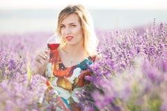 Schöne blonde sexy Frau trinkt roten trockenen Wein auf dem Lavendelgebiet Stockbild