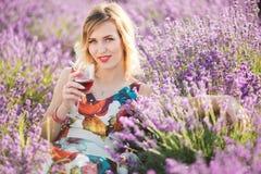 Schöne blonde sexy Frau trinkt roten trockenen Wein auf dem Lavendelgebiet Stockbilder