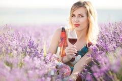 Schöne blonde sexy Frau trinkt roten trockenen Wein auf dem Lavendelgebiet Stockfotografie