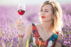 Schöne blonde sexy Frau trinkt Rotwein auf dem Lavendelgebiet Stockfotos