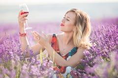 Schöne blonde sexy Frau trinkt Rotwein auf dem Lavendelgebiet Stockbilder