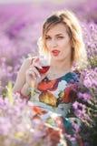 Schöne blonde sexy Frau trinkt Rotwein auf dem Lavendelgebiet Stockfoto