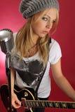Schöne blonde spielende elektrische Gitarre Stockfoto