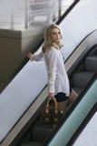 Schöne blonde städtische Frau auf Stadtrolltreppe Lizenzfreies Stockfoto