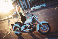 Schöne blonde Stellung der jungen Frau nahe einem Motorrad auf dem b Stockbild