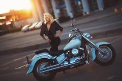Schöne blonde Stellung der jungen Frau nahe einem Motorrad auf dem b Stockfotografie
