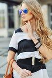 Schöne blonde tragende Sonnenbrille der jungen Frau - fashio im Freien Stockfotografie