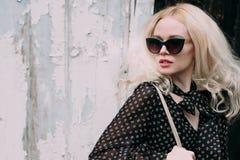 Schöne blonde tragende Sonnenbrille der jungen Frau, schwarzer Spitzen- und Bleistiftrock, Hut und Handtasche, stehend auf der St Lizenzfreies Stockbild