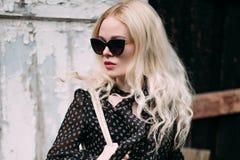 Schöne blonde tragende Sonnenbrille der jungen Frau, schwarzer Spitzen- und Bleistiftrock, Hut und Handtasche, stehend auf der St Stockfotos