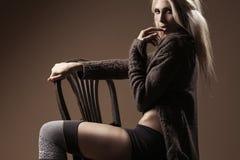 Schöne blonde tragende Wolljacke und Strümpfe auf dem Stuhl Stockfotografie