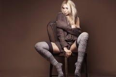 Schöne blonde tragende Wolljacke und Strümpfe auf dem Stuhl Lizenzfreie Stockfotos
