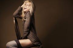Schöne blonde tragende Wolljacke und Strümpfe auf dem Stuhl Lizenzfreies Stockbild