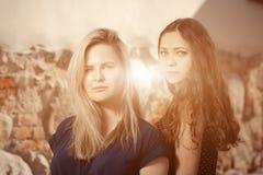 Schöne blonde und des Brunette junge Frauen, die auf die Straße gehen Aufflackern für Text und Design Lebensstilmädchen in der St Lizenzfreie Stockfotos