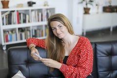 Schöne blonde und junge Frau, die auf einem Sofa unter Verwendung eines Phons sich entspannt Stockfoto