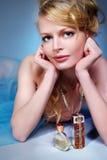 Schöne blonde und reizvolle Frau mit Duftstoff Stockfoto