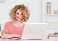 Schöne blonde weibliche Entspannung mit ihrem Laptop Lizenzfreie Stockbilder