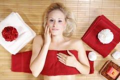 Schöne blonde wellnes Frau mit rotem deco Stockbild