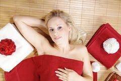 Schöne blonde wellnes Frau mit rotem deco Stockfotografie