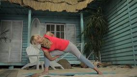 Schöne Blondine übt Yoga im modernen Studio stock footage