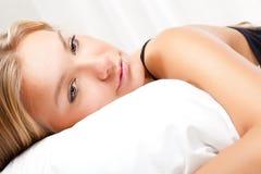 Schöne Blondine auf Bett Stockfoto