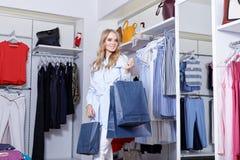 Schöne Blondine auf einem Einkaufen in einer Butike Stockfotos