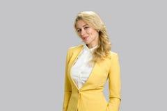 Schöne Blondine auf grauem Hintergrund Lizenzfreie Stockfotografie
