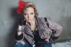Schöne Blondine in der Felsenart, die auf der Straße aufwirft Lizenzfreie Stockbilder