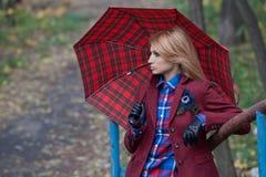 Schöne Blondine in der Jacke und in Lederhandschuhen, die umbr halten Lizenzfreie Stockfotografie