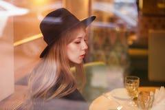 Schöne Blondine der jungen Frau im Hut bei Tisch in einem Restaurant durch Glas Reflexionen stockbild