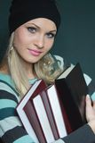 Schöne Blondine in der Strickjacke mit Büchern Lizenzfreie Stockbilder