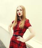 Schöne Blondine des Porträts, die rotes kariertes Kleid tragen Lizenzfreie Stockfotos