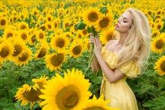 Schöne Blondine, die auf einer Wiese mit Sonnenblumen stehen lizenzfreie stockbilder