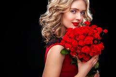 Schöne Blondine, die Blumenstrauß von roten Rosen halten Heilig-Valentinsgruß und internationaler Frauen ` s Tag, acht März Lizenzfreies Stockbild