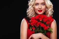 Schöne Blondine, die Blumenstrauß von roten Rosen halten Internationaler Frauen ` s Tag, acht März-Feier Lizenzfreies Stockbild