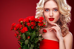 Schöne Blondine, die Blumenstrauß von roten Rosen halten Internationaler Frauen ` s Tag, acht März-Feier Stockfotografie