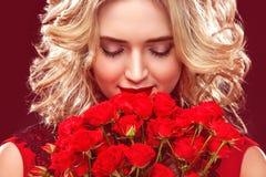 Schöne Blondine, die Blumenstrauß von roten Rosen halten Internationaler Frauen ` s Tag, acht März-Feier Stockbild