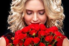 Schöne Blondine, die Blumenstrauß von roten Rosen halten Internationaler Frauen ` s Tag, acht März-Feier Lizenzfreies Stockfoto