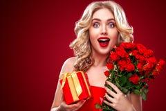 Schöne Blondine, die Blumenstrauß von roten Rosen und von Geschenk halten Heilig-Valentinsgruß und internationaler Frauen ` s Tag Stockfotografie