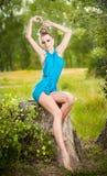 Schöne Blondine, die das blaue Kleid aufwirft auf einem Stumpf in einem grünen Wald tragen Lizenzfreie Stockfotos